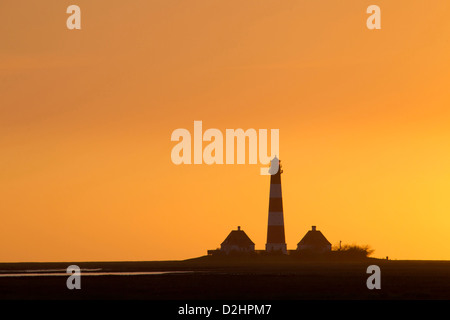 The lighthouse Westerheversand silhouetted against the evening sky. Peninsula of Eiderstedt, North Frisia, Germany - Stock Photo