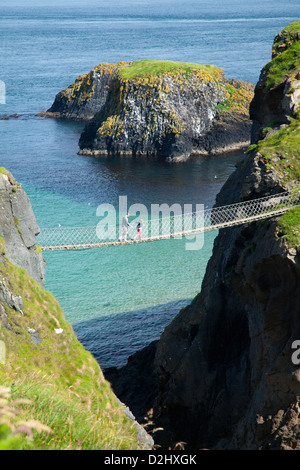People crossing Carrick-a-rede Rope Bridge, County Antrim, Northern Ireland. - Stock Photo