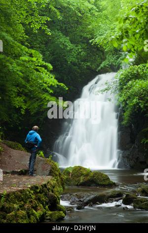 Person beneath Glenoe Waterfall, County Antrim, Northern Ireland. - Stock Photo