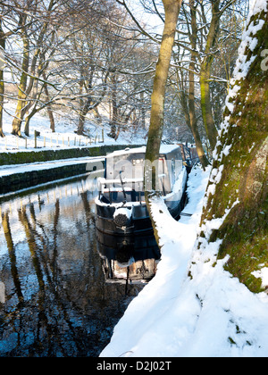 Barge moored up in winter on the Huddersfield Canal at Uppermill, Saddleworth, England, UK. - Stock Photo