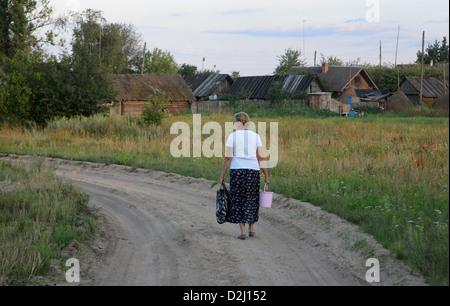 Kalnik Belarus, a woman walks along a country lane - Stock Photo