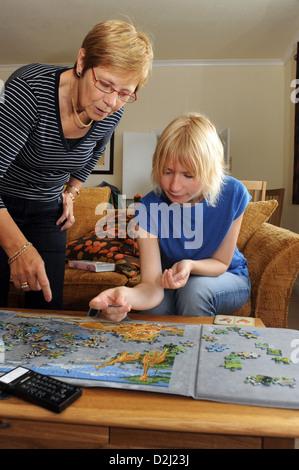 A young women with Learning Disabilities enjoys doing a jigsaw with her support worker, Skipton, North Yorkshire. - Stock Photo