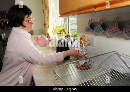 A young disabled  women makes tea in the kitchen, she lives independently with help from her carer. - Stock Photo