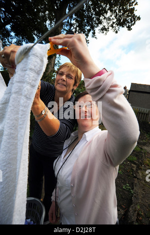 A young disabled  women hangs out her washing, she lives independently with help from her carer. - Stock Photo