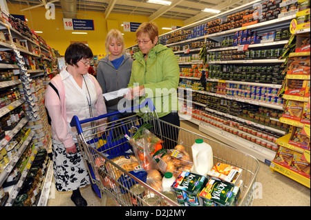 Two young women with Learning Disabilities go shopping with their support worker, Skipton, North Yorkshire. - Stock Photo