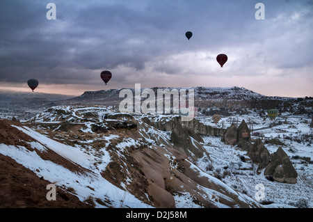 Hot air balloons take off in the early morning light over Göreme town in Cappadocia at winter, Central Anatolia - Stock Photo