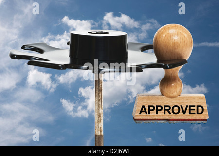 a stamp with the inscription approved hangs in a stamp rack, background sky and clouds - Stock Photo