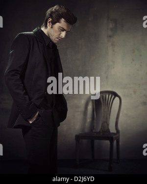 Handsome and calm man in a business suit on a dark background - Stock Photo