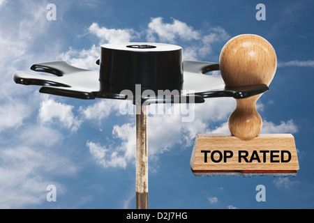 a stamp with the inscription top rated hangs in a stamp rack, background sky and clouds - Stock Photo