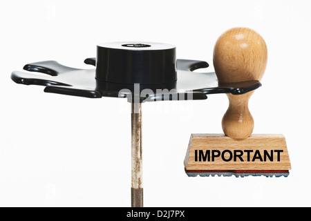 a stamp with the inscription important hangs in a stamp rack, background white - Stock Photo