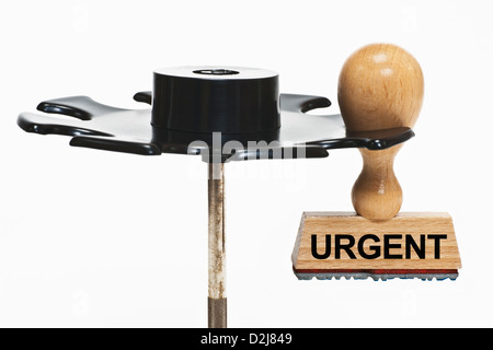 a stamp with the inscription urgent hangs in a stamp rack, background white - Stock Photo