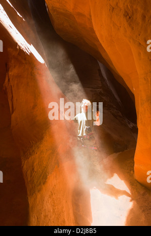 Man looking up into a sunbeam streaming into a slot-canyon; san rafael swell utah united states of america - Stock Photo