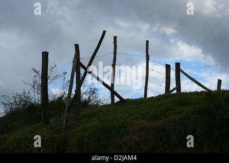 A wood and barbed wire fence stretching over a hill in a farmers pasture in Cotacachi, Ecuador - Stock Photo