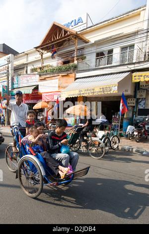 Phnom Penh, Cambodia, a woman with three children in a cyclo - Stock Photo