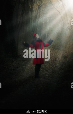 a woman in a red coat is standing in a dark forest in a spot of sunlight - Stock Photo