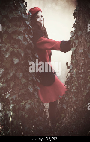 a woman with a red coat and hat between two trunks - Stock Photo
