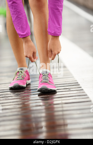Closeup of woman tying laces of running shoes before jogging on Brooklyn Bridge, New York, USA - Stock Photo