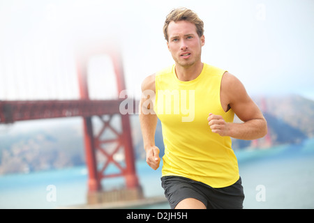 Male athlete runner working out jogging by Golden Gate Bridge, San Francisco, USA. Young fit Caucasian sport fitness - Stock Photo