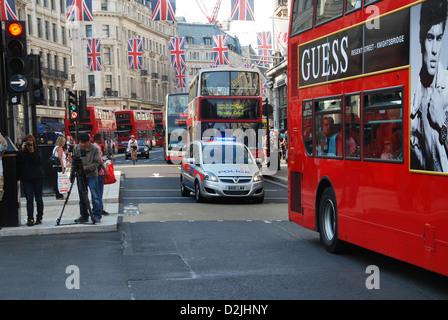 police car negotiating traffic, Regent Street London, UK - Stock Photo
