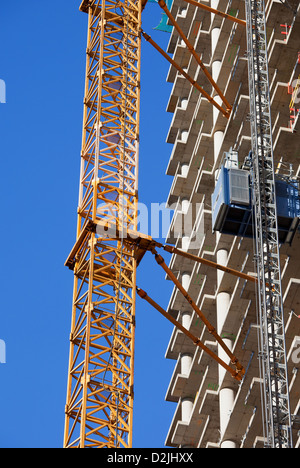 Modern apartment skyscraper under construction with cranes attached to it. - Stock Photo