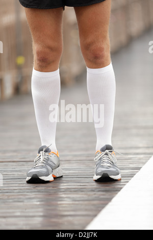 Running shoes and compression socks on male runner. Closeup of runner feet on Brooklyn Bridge, New York City - Stock Photo