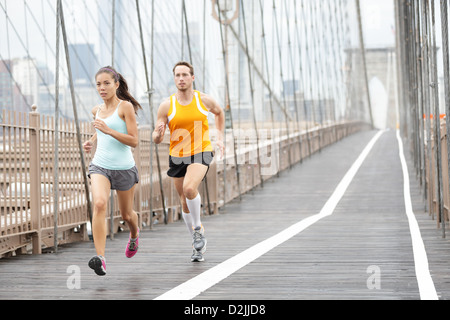 Full length of Asian woman and Caucasian man jogging on Brooklyn Bridge, New York City, USA - Stock Photo