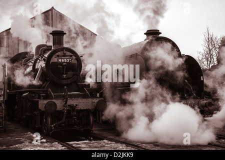 Steam locomotives outside engine shed Ivatt class number 46521 and King Arthur class Sir Lamiel number 30777 - Stock Photo