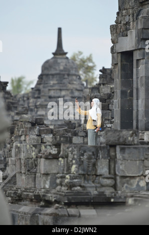 A veiled indonesian woman check his mobile phone in the temple of Candi Sewu at Prambanan; Yogyakarta, Java. Indonesia. - Stock Photo