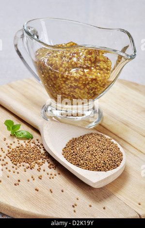 Mustard sauce in a gravy boat and mustard seeds in a wooden spoon - Stock Photo