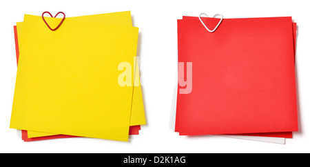 yellow and red sticky notes with paper clip in shape of heart on white background - Stock Photo