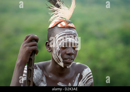 Portrait of Kara man with body painting and headdress-holding rifle - Stock Photo