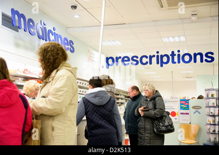 Prescriptions counter inside a Boots shop in Cwmbran, South Wales, UK. People queuing for over the counter medicines. - Stock Photo