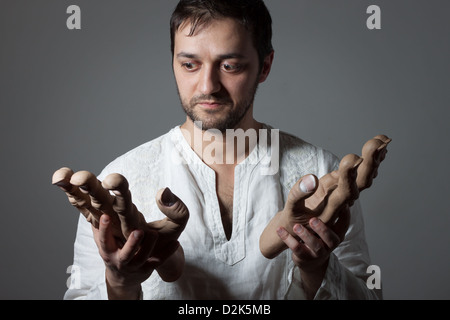 Young bearded man holding two huge mock hands on dark background - Stock Photo