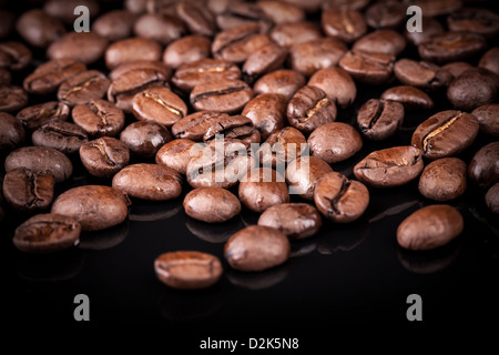Fresh roasted coffee beans on black shine table. Closeup photo - Stock Photo