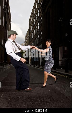 Couple lindy hop dancing in urban street - Stock Photo