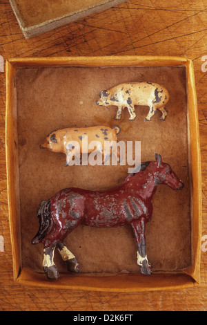 Small cardboard tray containing scratched lead models of two pigs and brown horse - Stock Photo