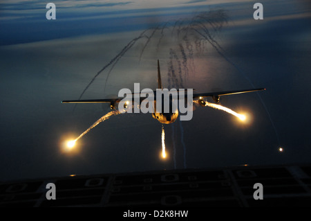 A C-130 night training mission uses live flares as an aerial infrared countermeasure used to defeat infrared homing - Stock Photo