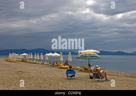 Row of beach chairs and sun umbrellas on a cloudy day at the beach - Stock Photo