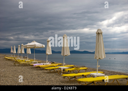 Dark clouds and vacant beach chairs at the beach - Stock Photo
