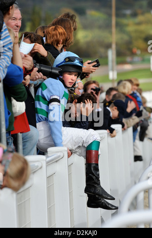 Young jockeys from the opening race watch other competitors in the 148cm and Under Charles Owen Pony Race Final - Stock Photo