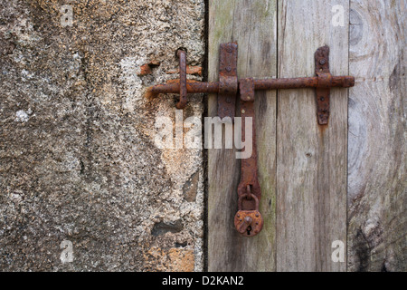An old and rusty padlock on a wooden door with a latch. - Stock Photo