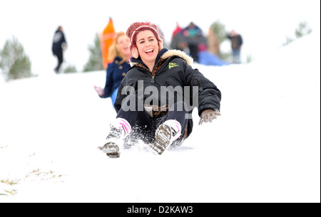 Two young women enjoying sledging together down a snow covered hill on a cold winters day. - Stock Photo