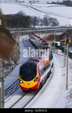 Tracks, trains & passengers on Virgin Pendolino passenger, high speed Train at Beckfoot, Cumbria in wintery conditions with snow covered track. UK