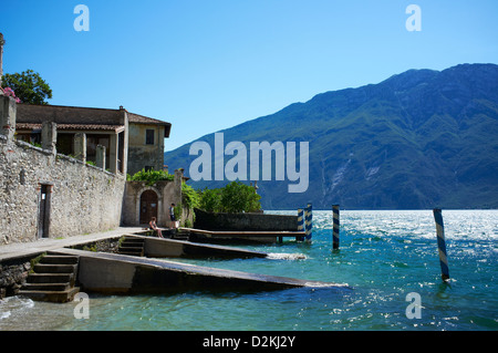 Small beach in Limone town with Monte Baldo in background - Stock Photo