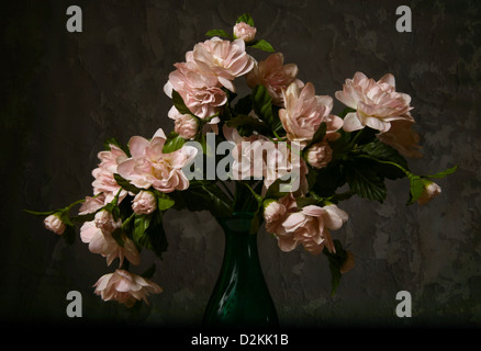 Artificial flowers on a background of an old wall - Stock Photo