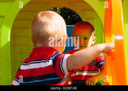 Two little brothers playing in the playhouse. - Stock Photo
