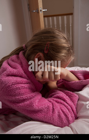 Young female wearing a pink dressing gown, hand covering her face. - Stock Photo