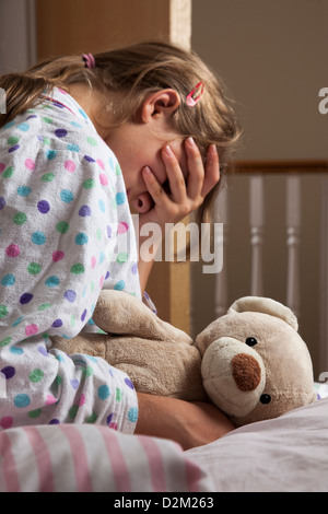Young female wearing a pajamas clutching her teddy bear, hand covering her face. - Stock Photo