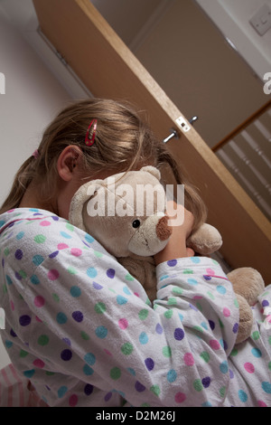 Young female wearing a pajamas clutching her teddy bear. - Stock Photo