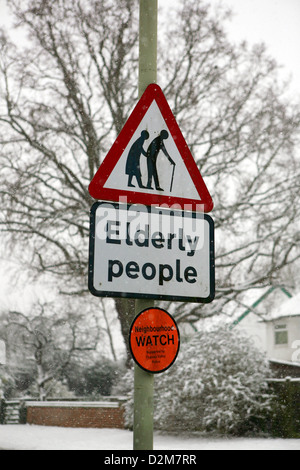 Kinneir & Calvert Elderly people warning road sign and Neighborhood Watch sign in Britain, bad weather snow all - Stock Photo